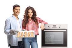 年轻加上烤箱和新近地被烘烤的曲奇饼盘子  库存图片