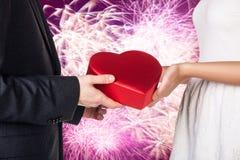 年轻加上的特写镜头手红色心形的礼物盒 免版税库存图片
