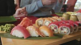 年轻加上筷子在一家日本餐馆采取从一块板材的寿司 影视素材
