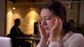 年轻劳累过度的女性办公室工作者特写镜头得到heache和被摧残和混淆 股票视频