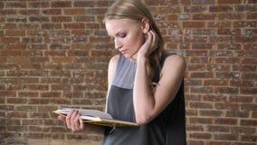 年轻包含的白肤金发的女孩是阅读书,砖背景 股票视频
