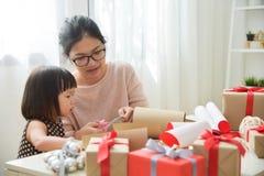 年轻包裹礼物盒的母亲和她的女儿 免版税图库摄影