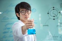 年轻化学家拿着玻璃圆锥形烧瓶用一种蓝色液体化工解答 免版税库存照片