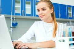 年轻化学老师在学校使用膝上型计算机特写镜头的实验室工作场所 免版税库存图片