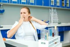 年轻化学老师在学校打呵欠实验室的工作场所 免版税库存照片