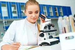 年轻化学老师在学校采取笔记的实验室工作场所 免版税图库摄影