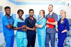 年轻医生多种族队在站立在手术室的医院 免版税库存图片