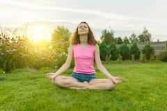 年轻十几岁的女孩实践的瑜伽,思考在夏天日落背景,在绿草,草坪在房子附近 库存照片