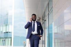 年轻千福年的CEO讲话与一个新的客户在办公室外 库存照片