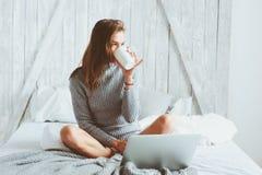 年轻博客作者或女商人在家与社会媒介,饮用的咖啡一起使用在清早在床上 图库摄影