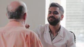 年轻印地安男性患者的医生皮肤病学家审查的眼珠 影视素材