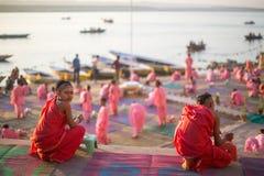 年轻印度修士举办仪式遇见在恒河的银行的黎明,并且升印地安旗 库存照片