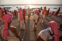 年轻印度修士举办仪式遇见在恒河的银行的黎明,并且升印地安旗 免版税库存照片