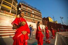 年轻印度修士举办仪式遇见在恒河的银行的黎明,并且升印地安旗 库存图片