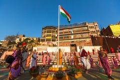 年轻印度修士举办仪式遇见在恒河的银行的黎明,并且升印地安旗 免版税库存图片