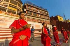 年轻印度修士举办仪式遇见在恒河银行的黎明,并且升印地安旗 免版税库存图片