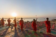 年轻印度修士举办仪式遇见在恒河银行的黎明,并且升印地安旗 库存图片