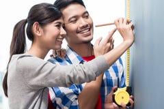 年轻印度尼西亚在新的公寓的夫妇测量的墙壁 库存图片