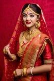 年轻印度新娘佩带的金首饰和红色莎丽服画象在婚礼 免版税库存照片