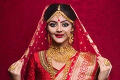 年轻印度新娘佩带的金首饰和红色莎丽服画象在婚礼 免版税图库摄影