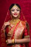年轻印度新娘佩带的金首饰和红色莎丽服画象在婚礼 免版税库存图片