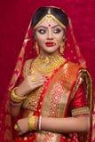 年轻印度新娘佩带的金首饰和红色莎丽服画象在婚礼 库存图片