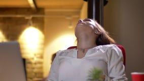 年轻卷发妇女乏味和疲乏斜倚在椅子和震动她的头发特写镜头画象在办公室 股票视频