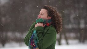 年轻卷曲女孩在公园 下雪,并且妇女在外套结冰了,不用帽子和手套 在围巾的套 影视素材
