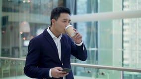 年轻发短信在电话的商人走的饮用的咖啡的慢动作 影视素材