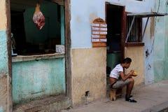 年轻古巴人坐吃在边路的凳子午餐 库存照片
