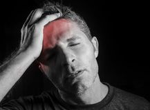 年轻可爱和哀伤的人遭受的头疼用在他的拍子头的手在看起来的重音绝望和病残被隔绝的黑色a 免版税库存图片