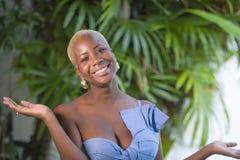 年轻可爱和快乐的黑人美国黑人的妇女微笑的愉快的摆在的快乐的在家大阳台生活方式画象与gre的 库存图片
