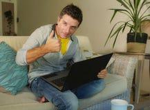 年轻可爱和愉快的人在家放松了研究坐在客厅沙发长沙发微笑的便携式计算机快乐作为  免版税库存照片