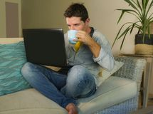 年轻可爱和愉快的人在家放松了研究坐在客厅沙发长沙发微笑的便携式计算机快乐作为  库存图片