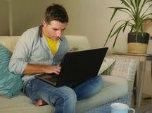 年轻可爱和愉快的人在家放松了研究坐在客厅沙发长沙发微笑的便携式计算机快乐作为  免版税图库摄影