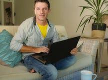 年轻可爱和愉快的人在家放松了研究坐在客厅沙发长沙发微笑的便携式计算机快乐作为  库存照片