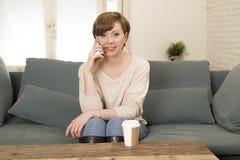 年轻可爱和愉快的红色头发妇女谈话沙发长沙发饮用的咖啡坐手机在communicat在家放松了 免版税库存照片