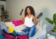 年轻可爱和疯狂的愉快的黑人美国黑人的妇女包装在手提箱的衣裳材料离开为假日做准备绊倒h 免版税库存图片