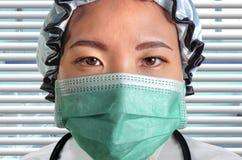 年轻可爱和确信的亚裔中药医生妇女接近的画象防护顶头盖帽面膜的 免版税库存照片