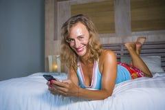年轻可爱和美丽的妇女在家在使用互联网社会媒介app的床上在手机微笑的愉快轻松 免版税图库摄影