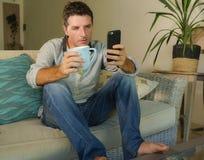年轻可爱和轻松的人在家使用坐在客厅沙发长沙发的手机饮用的咖啡约会或挥动o 免版税库存照片