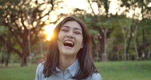 年轻可爱的亚裔妇女画象愉快地微笑入照相机在夏天公园对日落 股票录像