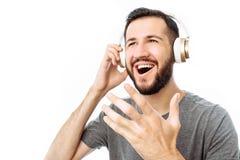 年轻可爱的人唱歌并且听到与耳机的音乐 免版税库存图片
