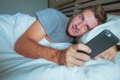 年轻可爱的人微笑的愉快说谎在床上在使用社会媒介app的晚上在手机发短信给或有录影电话在co 库存照片