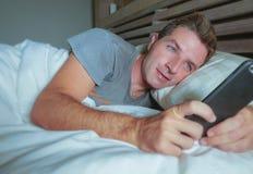 年轻可爱的人微笑的愉快说谎在床上在使用社会媒介app的晚上在手机发短信给或有录影电话在co 免版税库存照片