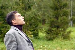 年轻可爱的人画象有一件灰色外套的,呼吸在新鲜的秋天空气在公园,显示他的面孔对风 Th 免版税库存照片