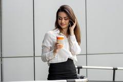 年轻可爱的企业夫人拿着一杯咖啡和谈话在电话 库存图片