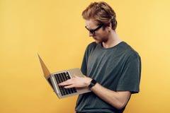 年轻可爱的使用膝上型计算机的人佩带的玻璃 图库摄影