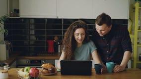 年轻可爱的卷曲愉快的白种人妇女在运作的厨房里坐膝上型计算机饮用的茶,她的丈夫来和 股票录像
