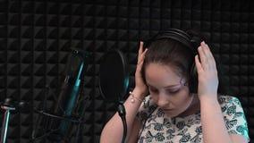 年轻可爱的唱歌的女孩在专业耳机投入 浪漫女歌手为唱歌做准备在专业声音 股票视频